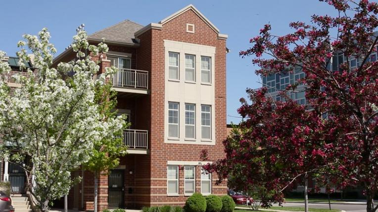 3 story townhome with trees in front